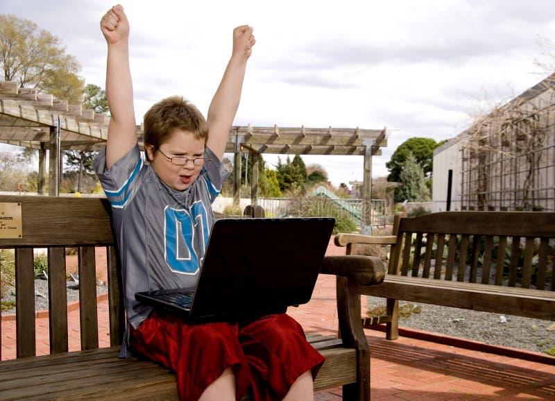 Menino de sorriso que usa um computador fotos de stock royalty free