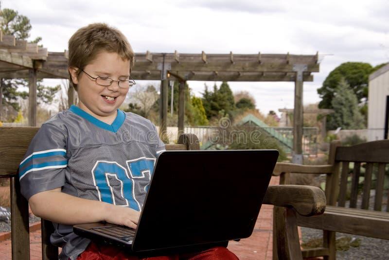 Menino de sorriso que usa um computador imagens de stock royalty free