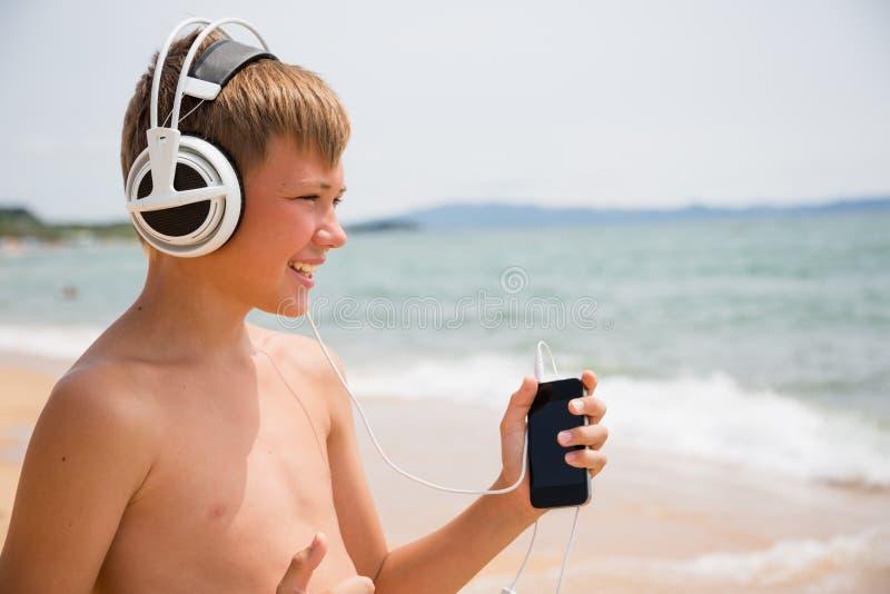 Menino de sorriso que usa um smartphone na praia imagens de stock