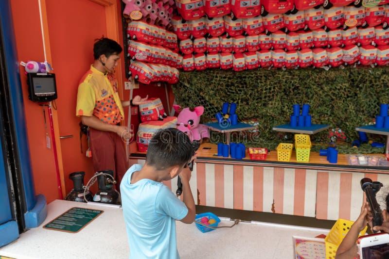 Menino de Ypung, tiros não reconhecíveis em latas de lata na batida das contagens do parque de diversões imagem de stock royalty free