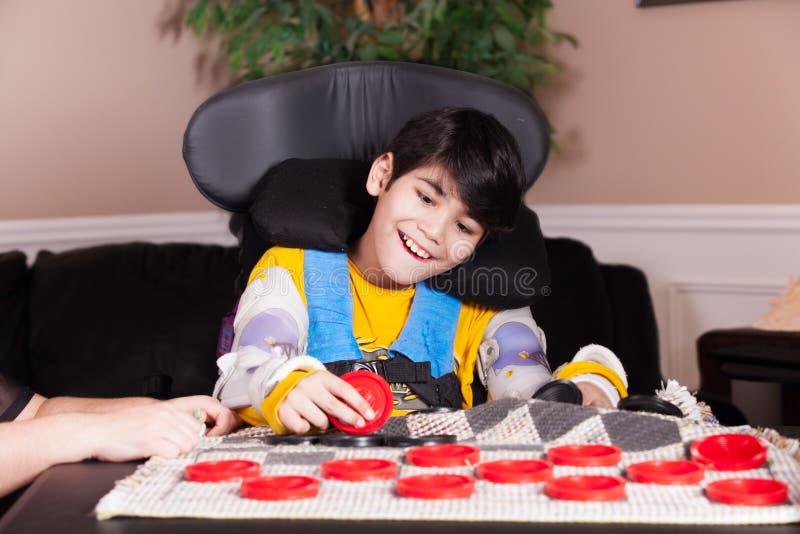 Menino deficiente dos jovens na cadeira de rodas que joga verificadores foto de stock