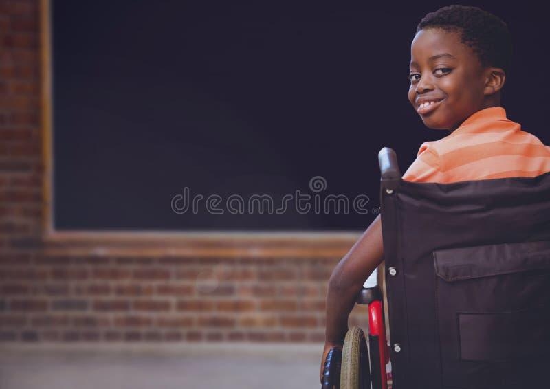 Menino deficiente na cadeira de rodas na sala de aula da escola fotografia de stock