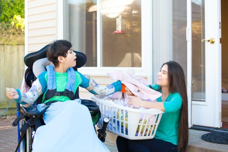 Menino deficiente na lavanderia mais velha de ajuda da dobra da irmã da cadeira de rodas fotografia de stock