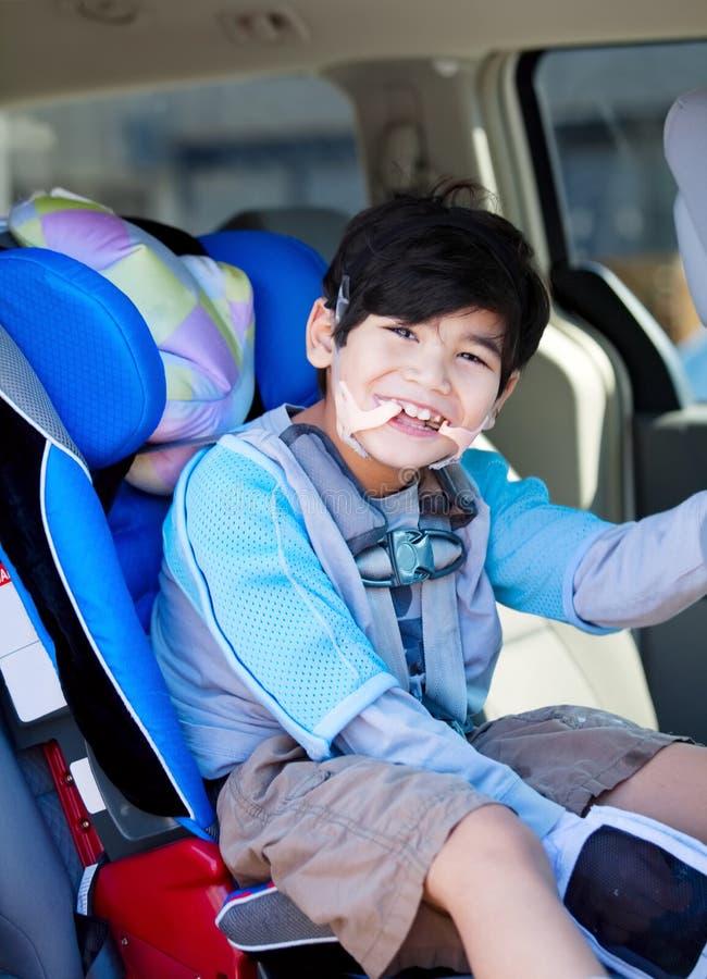 Menino deficiente que sorri ao sentar-se no carseat imagem de stock