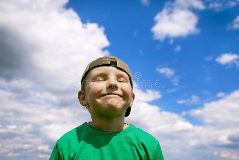 Menino despreocupado, sorrindo no céu azul e nuvens brancas Orgulhoso e satisfeito com si mesmo, um diabrete pequeno encantador R imagens de stock
