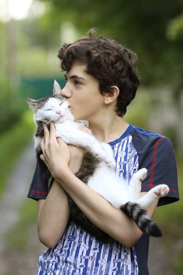 Menino do adolescente com abraço do beijo do afago do gato imagem de stock royalty free