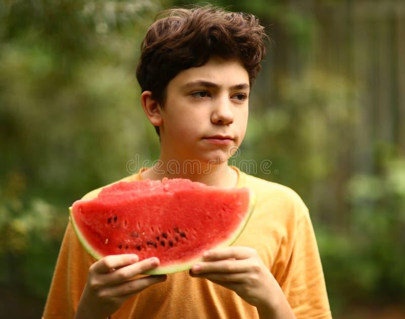 Menino do adolescente com fim cortado da melancia acima da foto imagem de stock