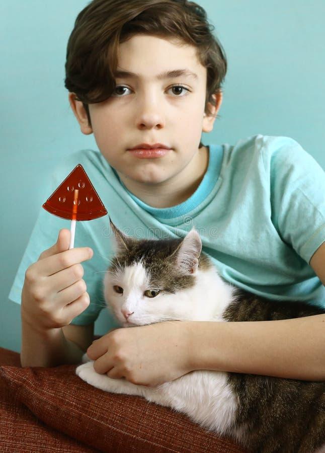 Menino do adolescente com os doces de açúcar da forma da melancia na vara foto de stock royalty free