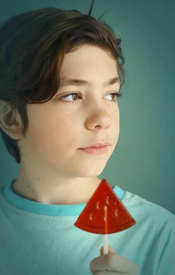 Menino do adolescente com os doces de açúcar da forma da melancia na vara imagens de stock