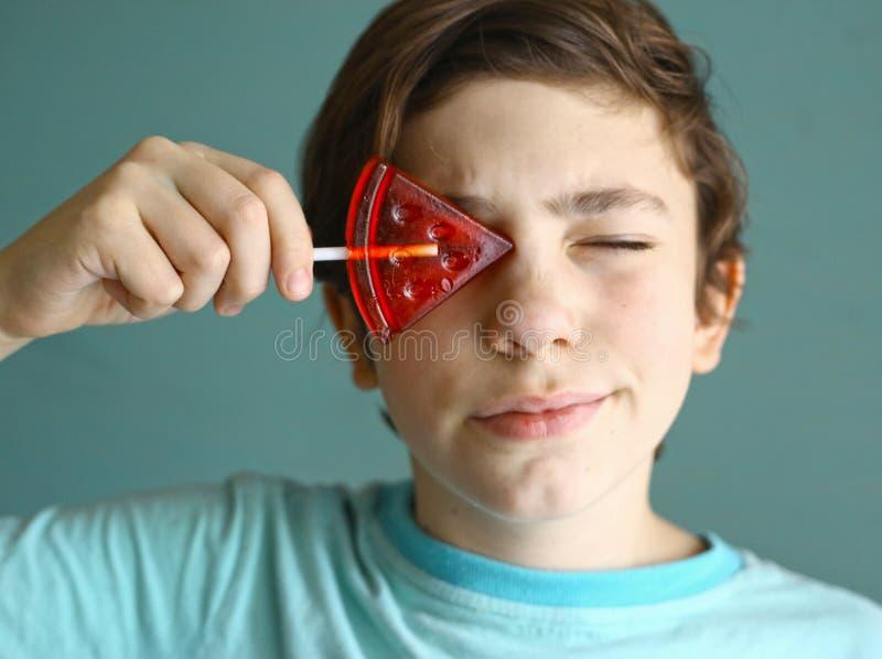 Menino do adolescente com os doces de açúcar da forma da melancia na vara imagens de stock royalty free