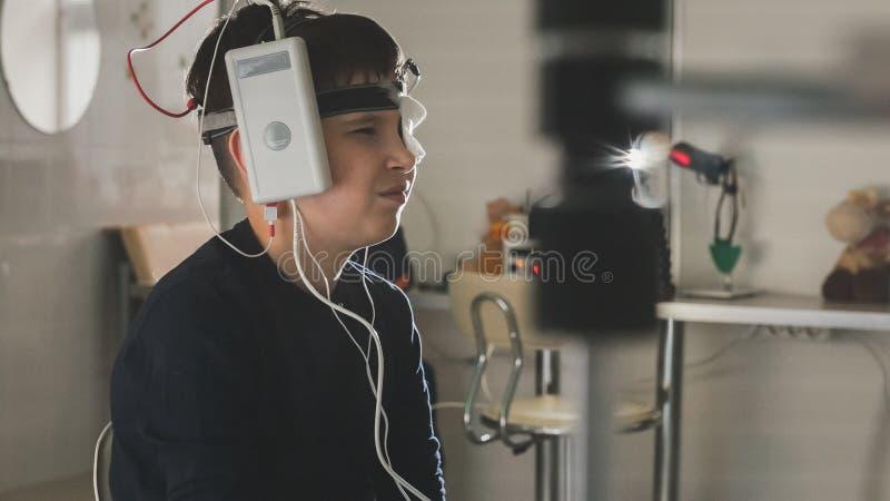 Menino do adolescente com os elétrodos na cabeça que olha ao monitor - diagnóstico do ` s das crianças dos cuidados médicos - oft fotos de stock royalty free