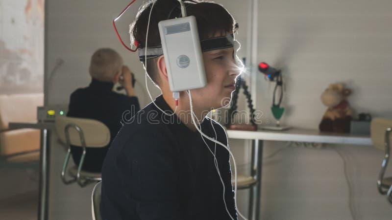 Menino do adolescente com os elétrodos na cabeça que olha ao monitor - diagnóstico do ` s das crianças dos cuidados médicos - oft fotografia de stock royalty free