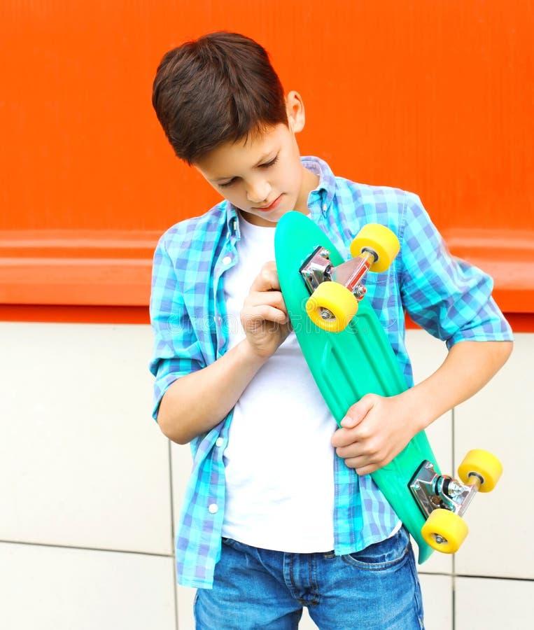 menino do adolescente com skate em uma camisa quadriculado na laranja foto de stock