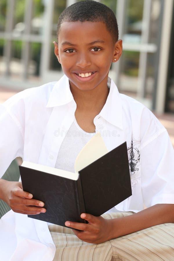 Menino do adolescente do americano africano que lê um livro fotos de stock