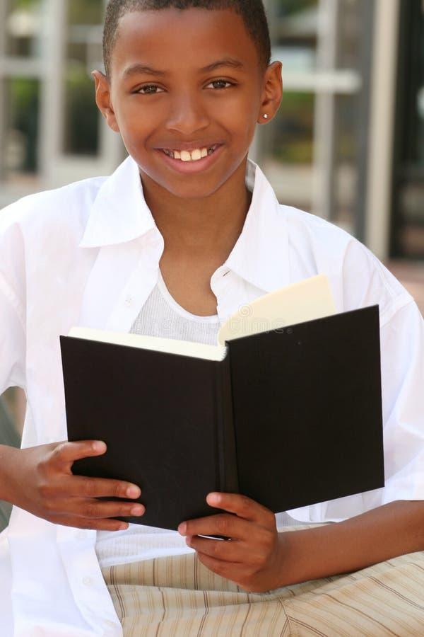 Menino do adolescente do americano africano que lê um livro fotografia de stock