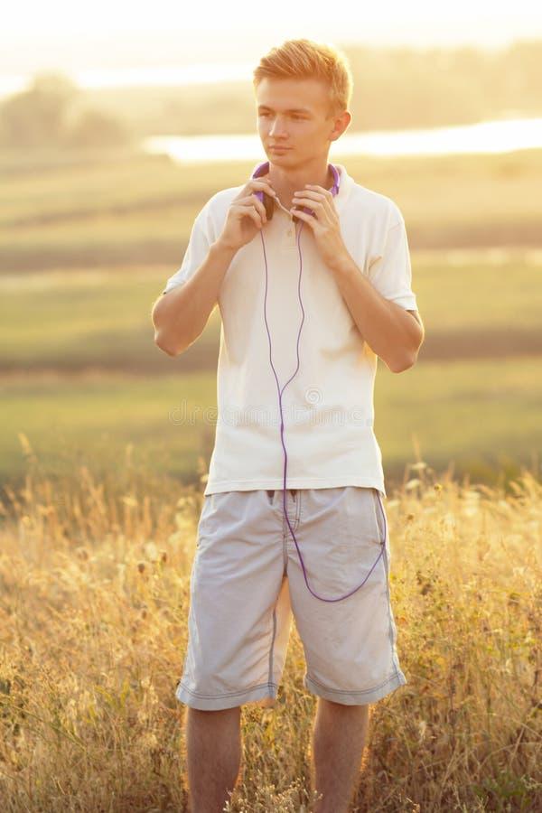 menino do adolescente nos fones de ouvido que escuta a música na natureza, no homem novo que descansam no campo, no esporte do co fotos de stock