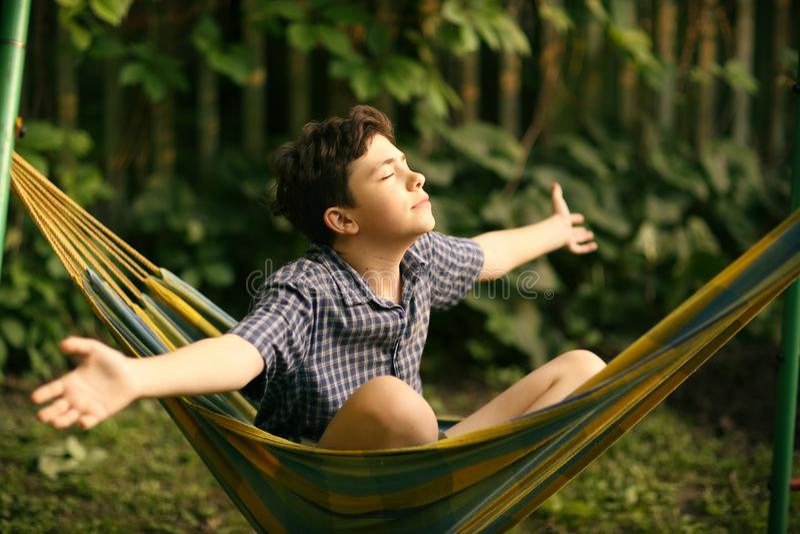 Menino do adolescente que descansa na rede imagens de stock royalty free