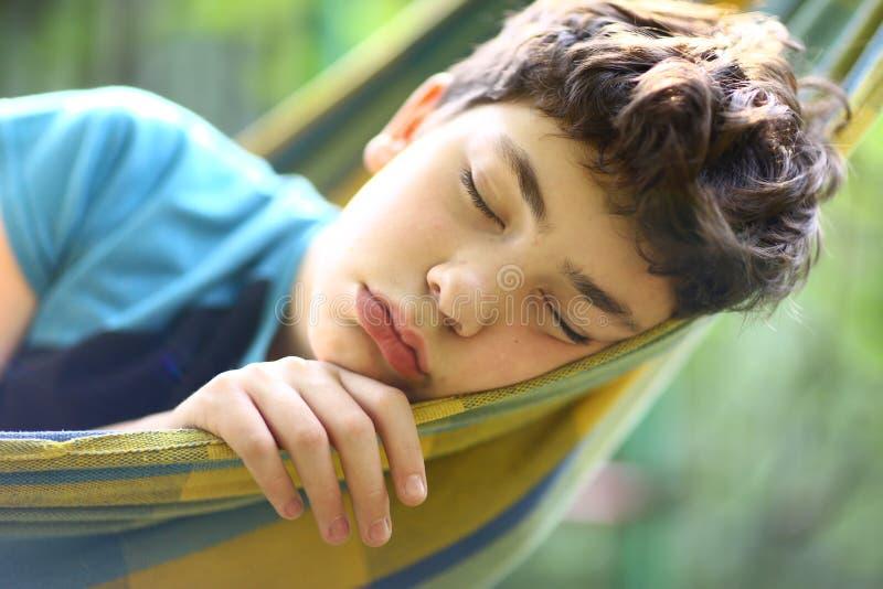 Menino do adolescente que descansa na rede fotos de stock