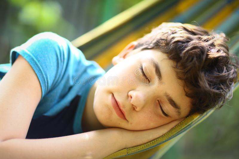 Menino do adolescente que descansa na rede fotografia de stock