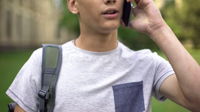 Menino do adolescente que fala no smartphone, boa cobertura móvel na cidade, uma comunicação foto de stock royalty free