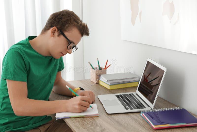 Menino do adolescente que faz seus trabalhos de casa na mesa foto de stock royalty free