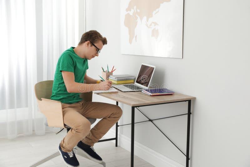 Menino do adolescente que faz seus trabalhos de casa na mesa imagens de stock royalty free