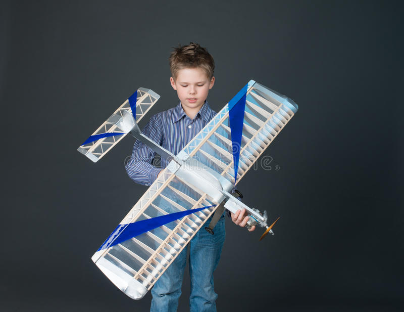 Menino do adolescente que guarda um modelo plano de madeira imagens de stock royalty free