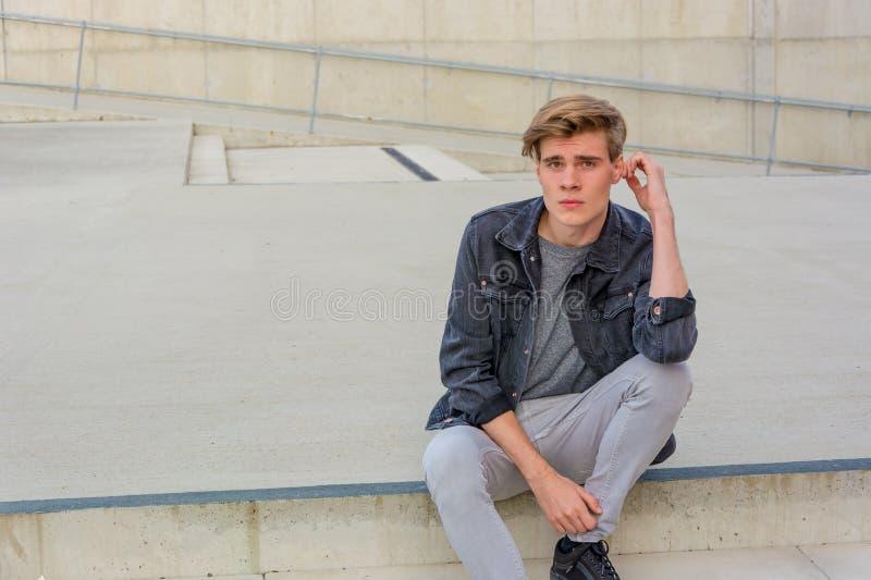 Menino do adolescente que senta-se no pensamento das escadas fotografia de stock