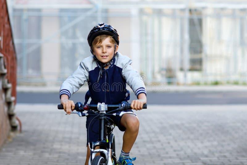 Menino do aluno na equitação do capacete de segurança com a bicicleta na cidade com trouxa Criança feliz na roupa colorida que bi foto de stock