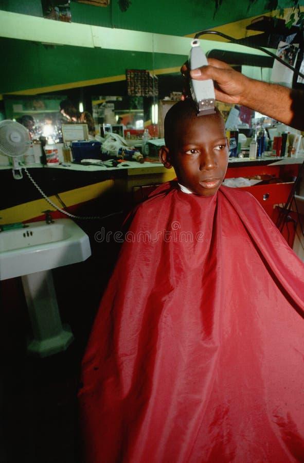 Menino do americano africano na cadeira de barbeiro fotos de stock royalty free