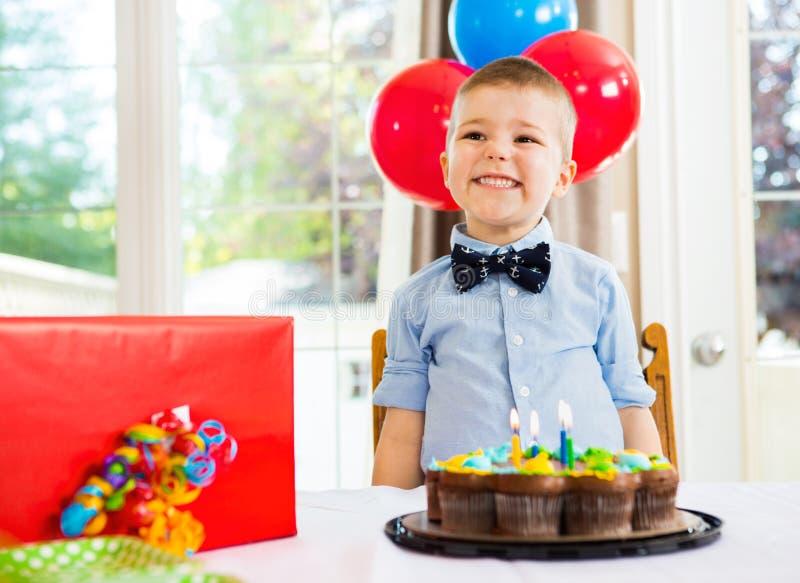 Menino do aniversário com bolo e presente na tabela fotos de stock