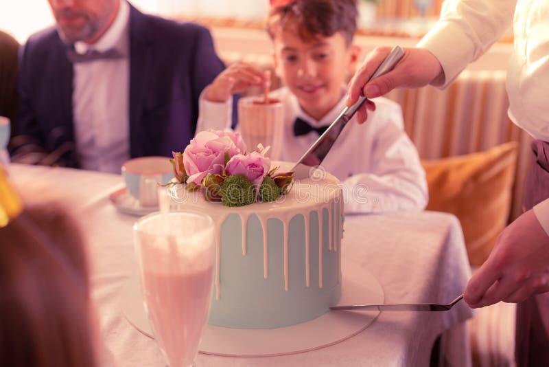 Menino do aniversário que olha o garçom que corta o bolo saboroso agradável imagem de stock royalty free