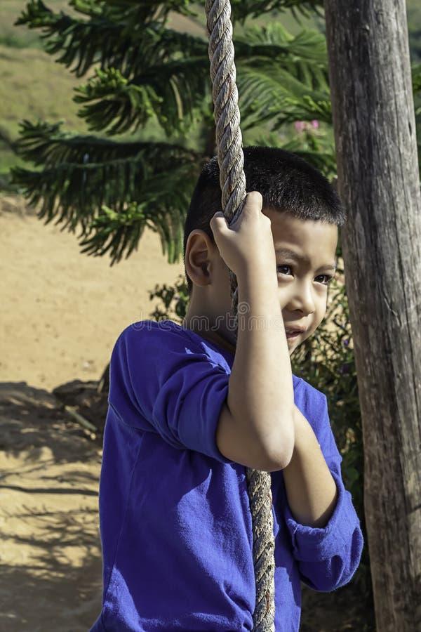 Menino do Asean nos nós a corda e sorriso felizmente fotografia de stock royalty free