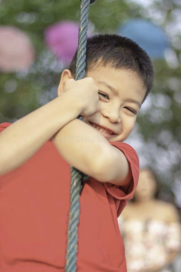 Menino do Asean nos nós a corda e sorriso felizmente imagem de stock royalty free