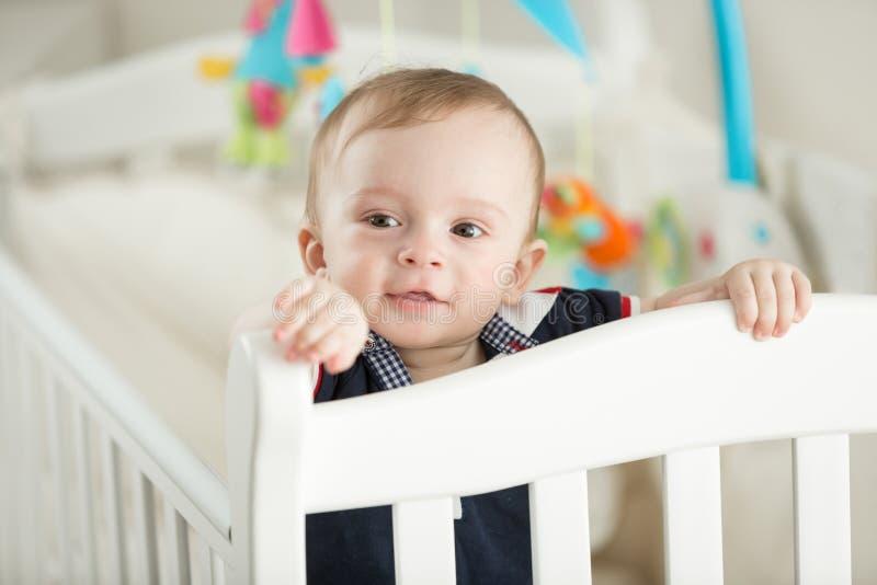 Menino do bebê de nove meses que sai os dentes e que levanta no berço branco fotografia de stock royalty free