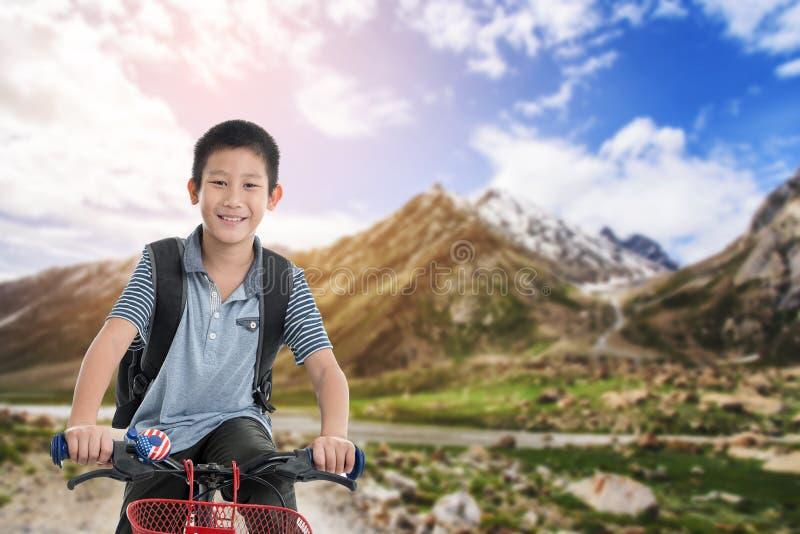 Menino do ciclismo com fundo do monte da aventura fotos de stock