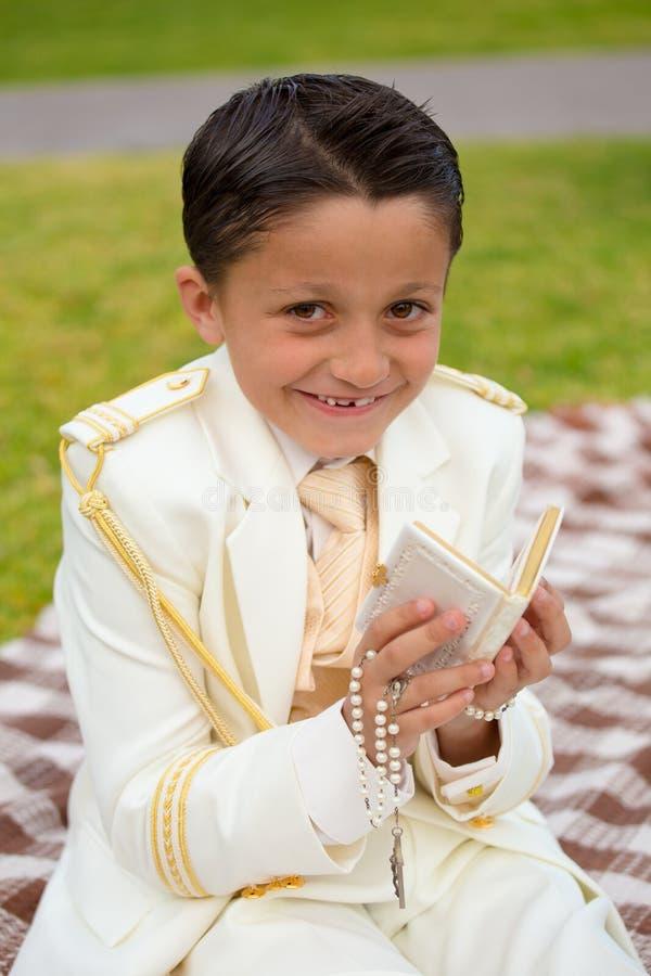 Menino do comunhão dos jovens primeiro que sorri com livro de oração e rosário fotos de stock
