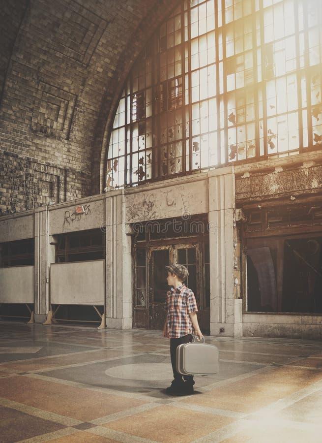 Menino do curso que procura o sentido na estação velha foto de stock royalty free
