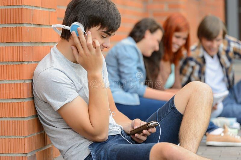 Menino do estudante com os amigos dos fones de ouvido fora do terreno imagens de stock