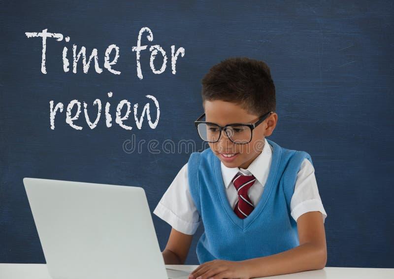 Menino do estudante na tabela usando um computador contra o quadro-negro azul com hora para o texto da revisão ilustração royalty free