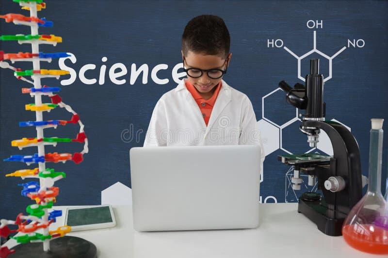 Menino do estudante na tabela usando um computador contra o quadro-negro azul com texto e gráficos da ciência imagem de stock