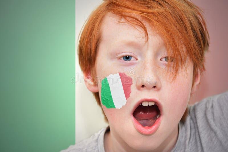 Menino do fã do ruivo com a bandeira italiana pintada em sua cara imagem de stock