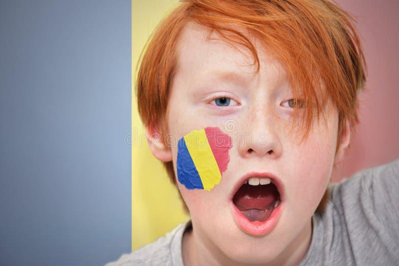 Menino do fã do ruivo com a bandeira romena pintada em sua cara fotografia de stock royalty free