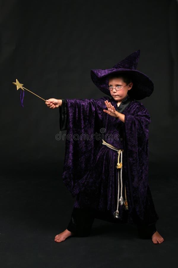 Menino do feiticeiro com a varinha mágica que molda um encanto imagens de stock royalty free