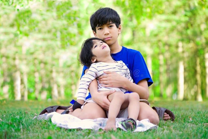 Menino do jovem adolescente que importa-se com o irmão deficiente fotografia de stock royalty free