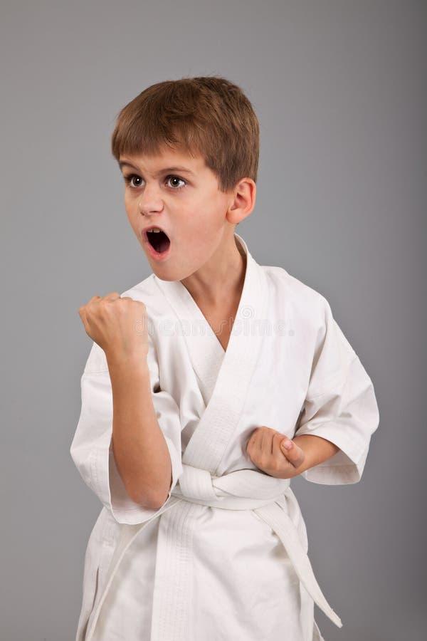 Menino do karaté na luta branca do quimono imagens de stock