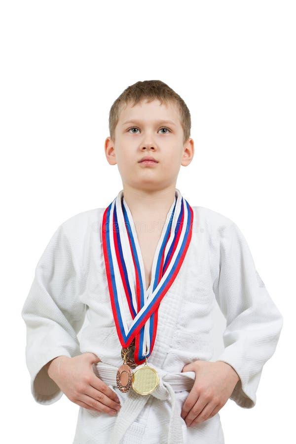Menino do karaté no quimono branco com luta das medalhas imagens de stock royalty free