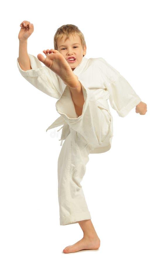 Menino do karaté que retrocede pelo pé esquerdo imagem de stock