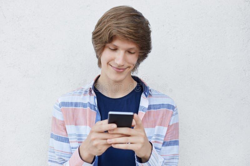 Menino do moderno que guarda mensagens de datilografia do telefone esperto a sua amiga que tem a expressão satisfeito que diz lhe fotos de stock