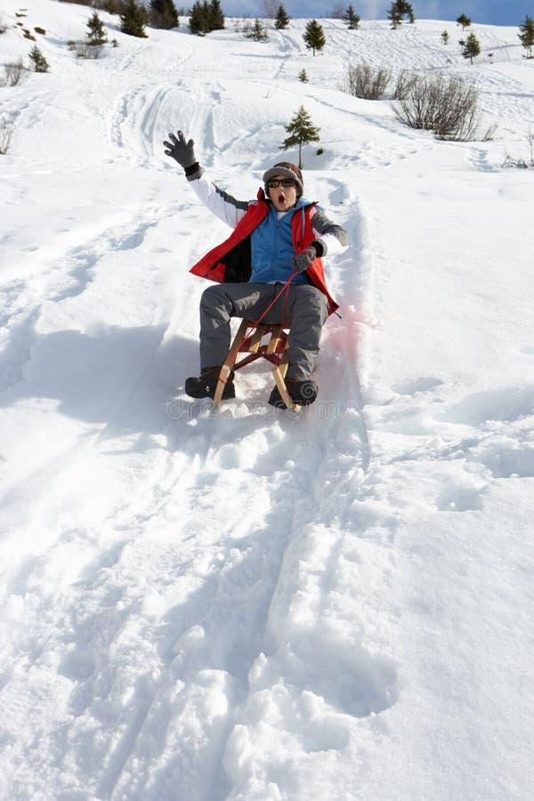 Menino do Pre-teen em um trenó na neve foto de stock